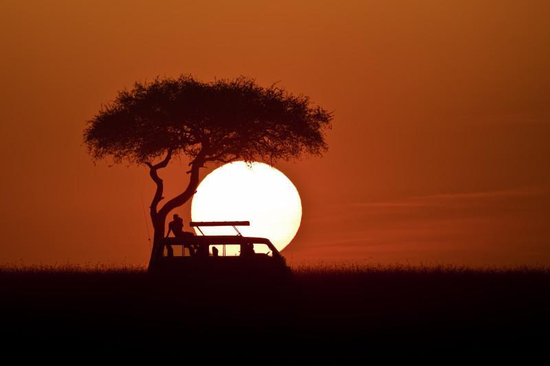 Sunset with safari car silhouette at Masai Mara