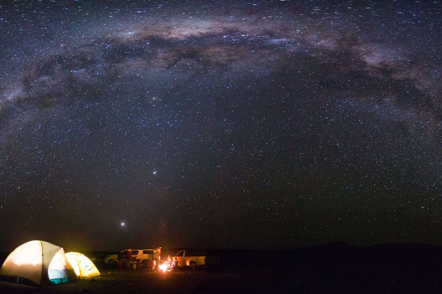Panoramic view of the milkyway over tents of campers camping under the stars in the middle of the karoo in south africa